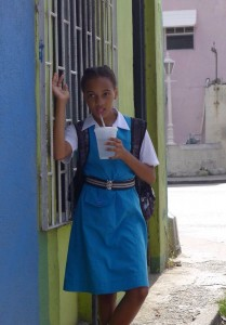School girl in her uniform sipping on an after school drink.